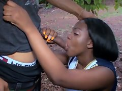 Raunchy ebony cheerleader licks prick outdoors