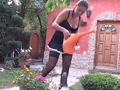Alluring married woman watering the plants and masturbating