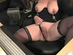 Attractive mature in nipple clamps at her desk