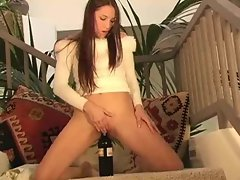 Filthy gal stuffing wine bottle in her vagina