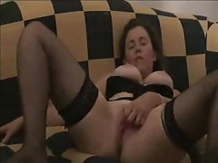 Buxom and on the couch rubbing her clit