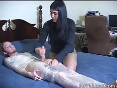 Dude in plastic wrap stroked by clothed young lady