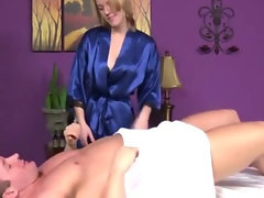 Dark haired masseuse rubs customers penis