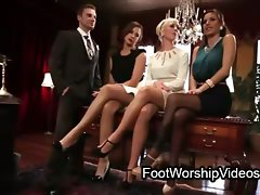 Lad caressing feet to three secretaries
