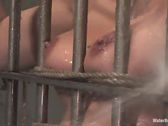 Convict nympho Delilah Strong tied to the bars and taking a nice hosing