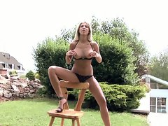 Clara G in ebony lingerie seducing on chair outdoor