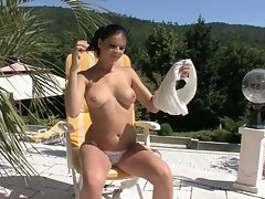 Tasty vixen playing with her knockers by the pool