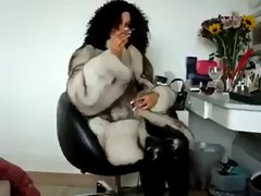 Fur mistress in boots and latex smoking