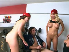 Three girls with red hats and large tits are hovering over a cock